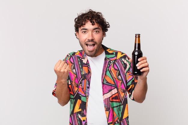 Homem hispânico com cerveja se sentindo chocado, animado e feliz, rindo e comemorando o sucesso, dizendo uau!