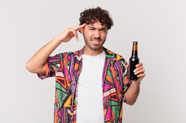 Homem hispânico com cerveja se sentindo confuso e perplexo, mostrando que você é louco, louco ou maluco