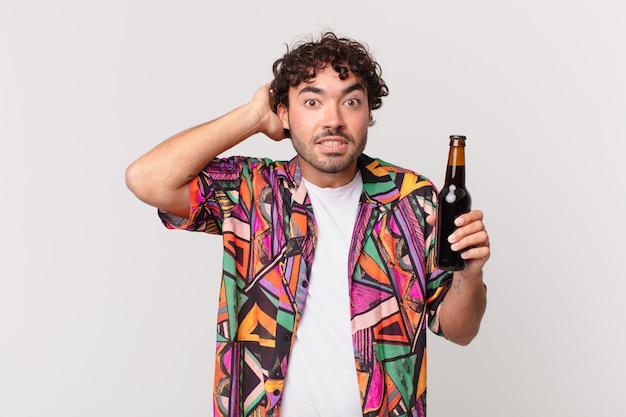 Homem hispânico com cerveja se sentindo estressado, preocupado, ansioso ou com medo, com as mãos na cabeça, entrando em pânico com o engano