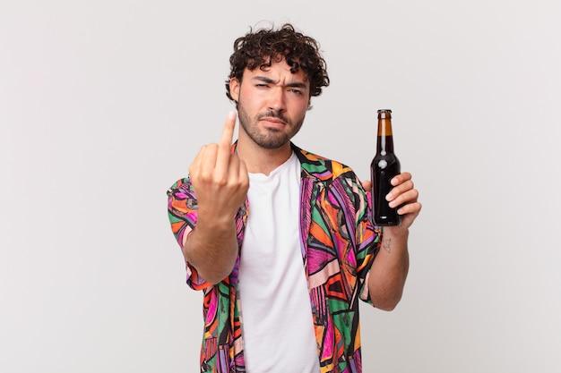Homem hispânico com cerveja se sentindo irritado, irritado, rebelde e agressivo, sacudindo o dedo do meio e revidando