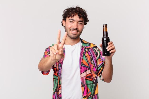 Homem hispânico com cerveja sorrindo e parecendo amigável, mostrando o número dois ou o segundo com a mão para a frente, em contagem regressiva
