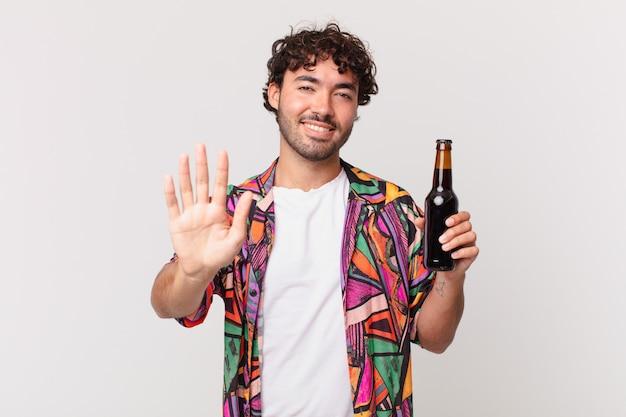 Homem hispânico com cerveja sorrindo feliz e alegre, acenando com a mão, dando as boas-vindas e cumprimentando você ou dizendo adeus