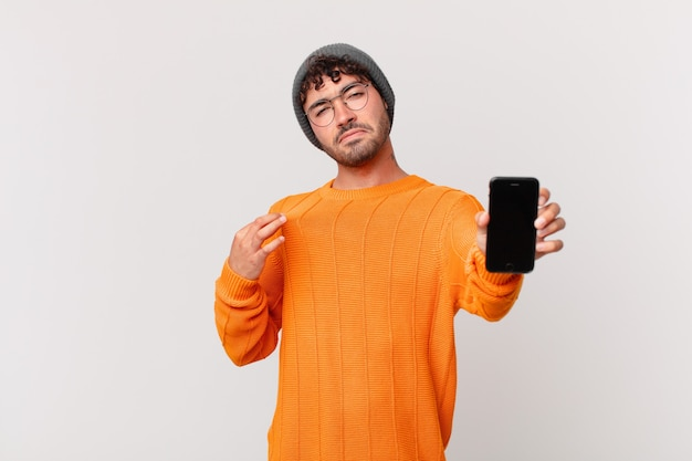 Homem hispânico com um celular que parece arrogante, bem-sucedido, positivo e orgulhoso, apontando para si mesmo