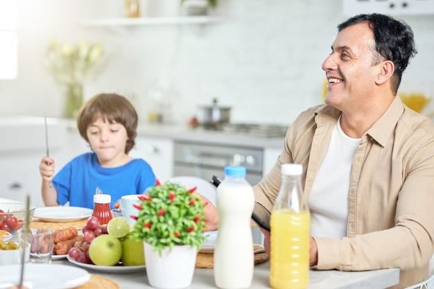 Homem hispânico de meia idade alegre sorrindo, enquanto toma o café da manhã com sua família, sentado à mesa da cozinha perto de seu filho em casa. família, paternidade, conceito matinal