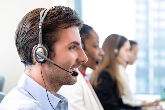 Homem hispânico, em, centro call center, com, equipe