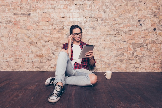 Homem hispânico feliz sentado no chão com um tablet e falando ao telefone