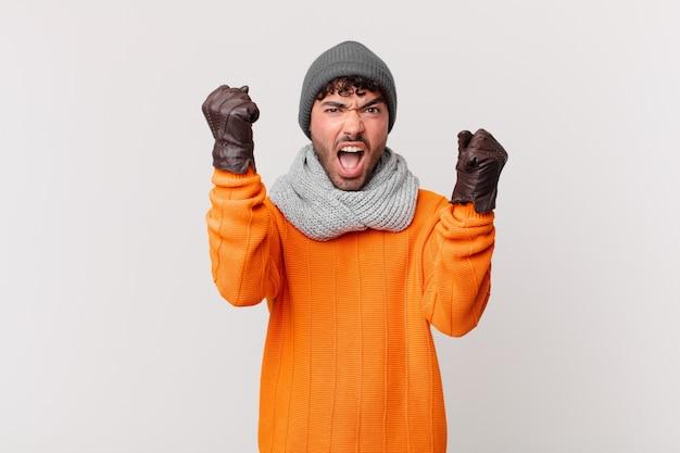 Homem hispânico gritando agressivamente com uma expressão de raiva ou com os punhos cerrados celebrando o sucesso