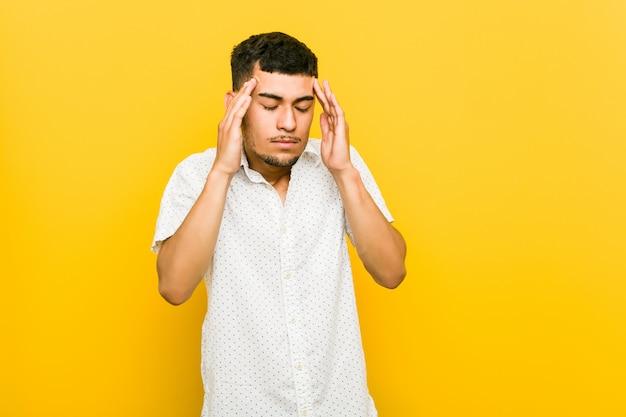 Homem hispânico jovem tocando templos e tendo dor de cabeça.