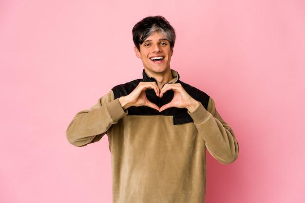 Homem hispânico magro jovem sorrindo e mostrando uma forma de coração com as mãos.