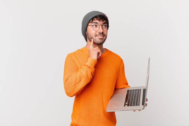 Homem hispânico nerd com um laptop