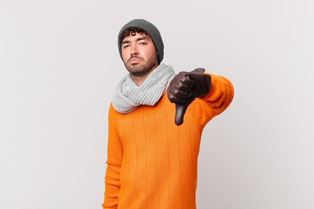 Homem hispânico se sentindo zangado, irritado, irritado, desapontado ou descontente, mostrando o polegar para baixo com um olhar sério
