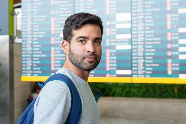 Homem hispânico sério posando perto de placa de partida
