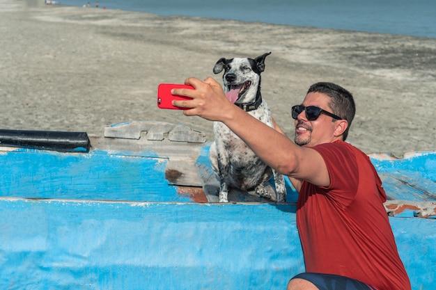 Homem hispânico tirando uma selfie com seu cachorro na praia no verão