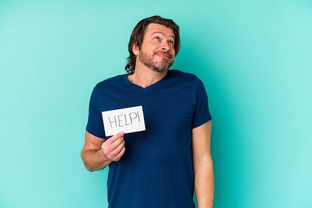 Homem holandês de meia-idade segurando um cartaz de ajuda isolado em um fundo azul, sonhando em alcançar objetivos e propósitos