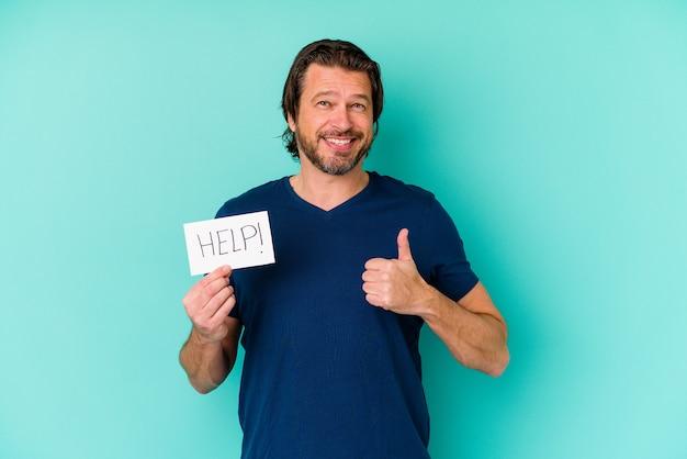 Homem holandês de meia-idade segurando um cartaz de ajuda isolado em um fundo azul, sorrindo e levantando o polegar