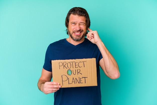 Homem holandês de meia-idade segurando um cartaz de proteger nosso planeta isolado no fundo azul, cobrindo as orelhas com as mãos.