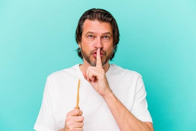 Homem holandês de meia-idade segurando uma escova de dentes isolada em um fundo azul, mantendo um segredo ou pedindo silêncio.