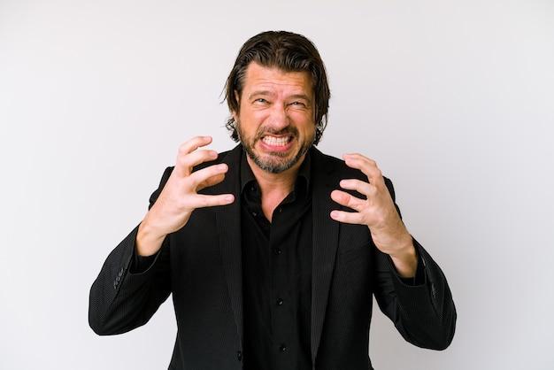 Homem holandês de negócios de meia-idade isolado na parede branca chateado gritando com as mãos tensas.