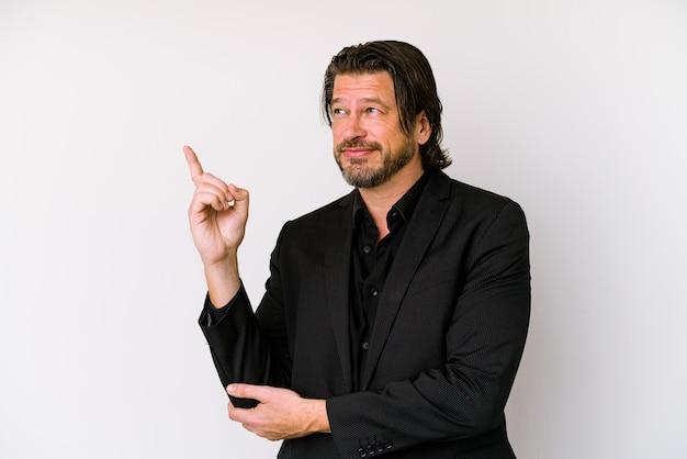 Homem holandês de negócios de meia-idade isolado no fundo branco, sorrindo alegremente, apontando com o dedo indicador de distância.