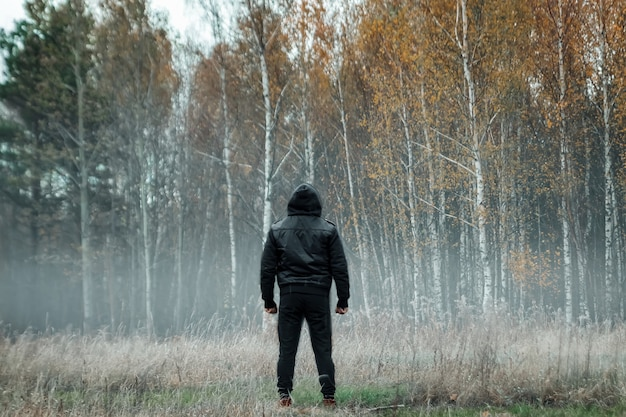 Homem, homem com um casaco preto no nevoeiro