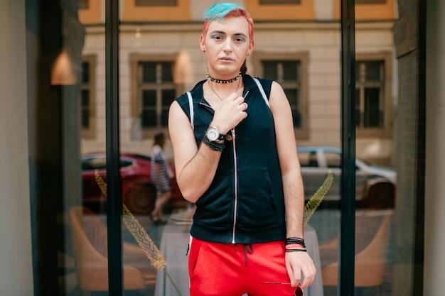 Homem homoxesual com maquiagem e penteado colorido em roupas elegantes, posando ao ar livre em frente a janela na rua.