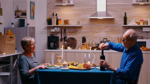 Homem idoso abrindo uma garrafa de vinho tinto durante um jantar romântico. casal idoso sênior conversando, sentado à mesa na cozinha, apreciando a refeição, comemorando seu aniversário em casa com comida saudável.