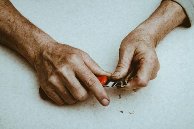 Homem idoso afia lápis com faca de escritório
