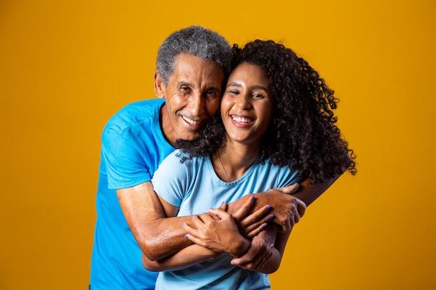 Homem idoso afro abraçando sua adorável filha em fundo amarelo. dia dos pais