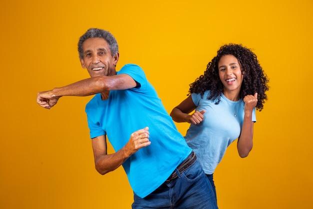 Homem idoso afro com sua filha dançando.
