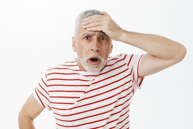Homem idoso ansioso e chocado lembra de algo, tapa na testa preocupado