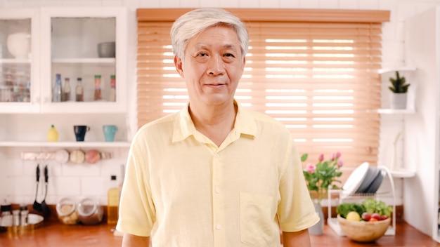 Homem idoso asiático que sente feliz sorrindo e olhando à câmera quando relaxe na cozinha em casa.
