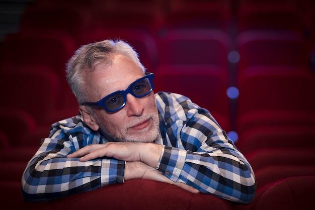 Homem idoso assistindo filme no cinema
