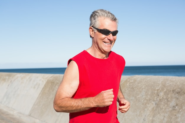 Homem idoso ativo jogging no pier