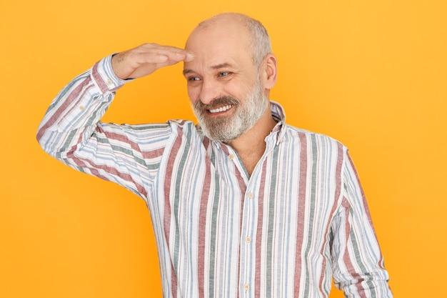 Homem idoso atraente e alegre com barba grisalha e careca posando isolado, mantendo a mão sobre os olhos para se proteger