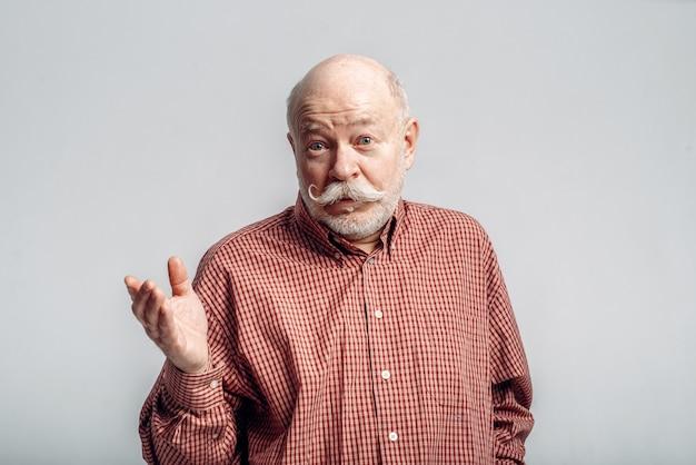 Homem idoso barbudo com bigode fica em uma camisa.
