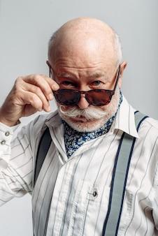 Homem idoso barbudo com poses de bigode em óculos de sol. idoso maduro