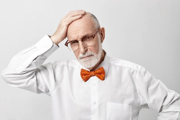 Homem idoso barbudo estressado e frustrado com roupas bonitas comemorando aniversário, mas sofrendo de uma terrível dor de cabeça