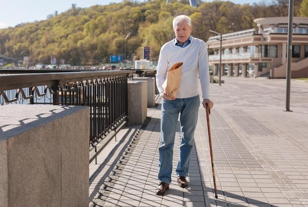 Homem idoso, bonito e relaxado, relaxando ao ar livre e caminhando enquanto carrega produtos para sua esposa