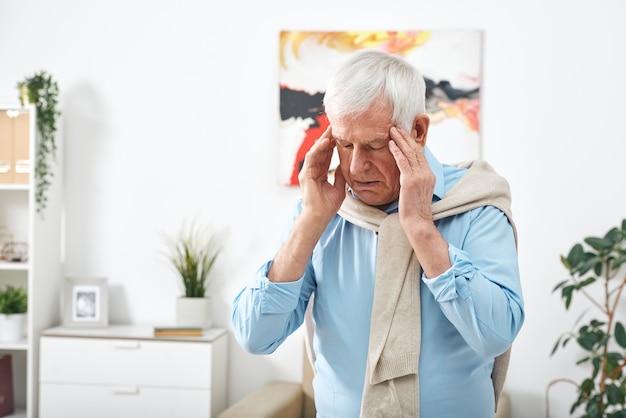 Homem idoso cansado de camisa azul tocando as têmporas enquanto sente dor de cabeça depois de trabalhar em casa