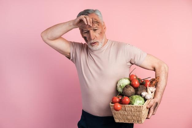 Homem idoso cansado segurando uma cesta com legumes em uma parede rosa
