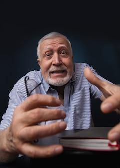 Homem idoso carismático, estende as mãos na moldura, como se quisesse agarrar alguém