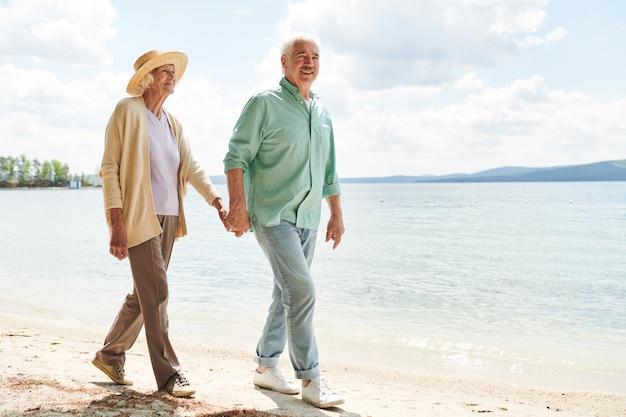Homem idoso casual e mulher segurando as mãos enquanto relaxa na praia ao longo da costa em um dia quente de verão
