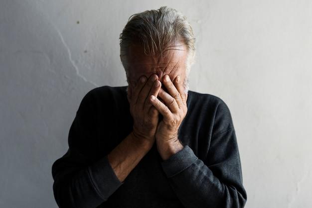 Homem idoso caucasiano cobrindo seu rosto