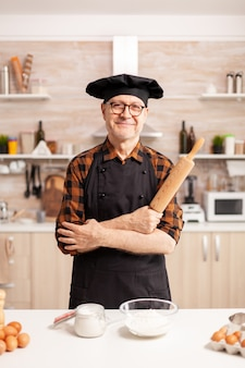 Homem idoso caucasiano usando avental na cozinha de casa sorrindo