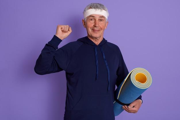 Homem idoso, cerrando o punho e segurando o tapete de ioga, vestindo roupas de esporte e bandana, posando isolado sobre lilás