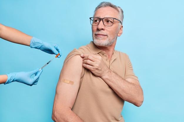 Homem idoso com barba grisalha envolvido em programa de vacinação gratuito recebe vacina no braço ouve atentamente o conselho da enfermeira usa óculos, camiseta bege, posa contra a parede azul