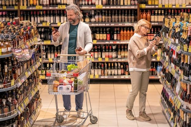 Homem idoso com carrinho de compras escolhendo conhaque enquanto sua esposa pegando uma garrafa de champanhe no departamento de bebidas alcoólicas de um supermercado