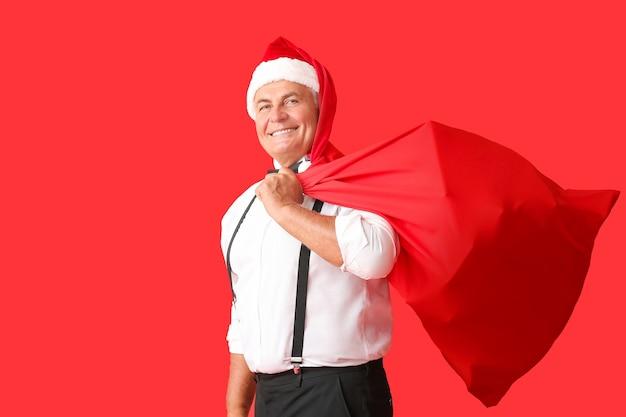 Homem idoso com chapéu de papai noel e com bolsa. celebração do natal