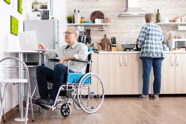 Homem idoso com deficiência em cadeira de rodas, trabalhando em casa, no laptop na cozinha, enquanto a esposa está preparando o café da manhã. empresário com deficiência, paralisia do empresário com deficiência para idoso aposentado.