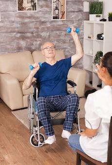 Homem idoso com deficiência em treinamento em cadeira de rodas com halteres durante a reabilitação com enfermeira